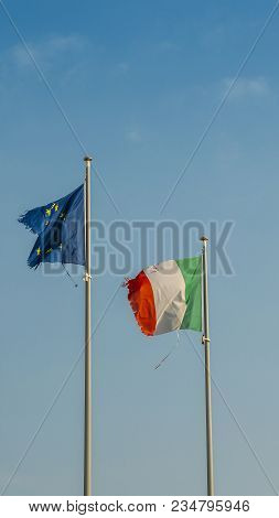 Italy Flag And Europe Flag Waving Together On A Mast In Isolated The Blue Sky Background. Concept Fo