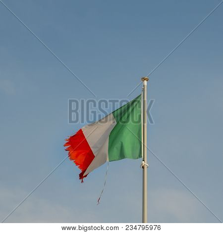Italian Flag On The Mast Blowing In The Wind With Ripped Corners, Perhaps A Metaphor For A Series Of