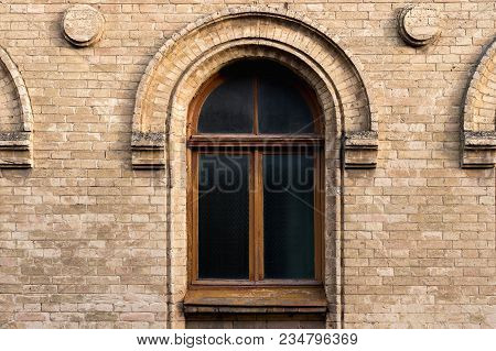 Vintage Arched Window In The Wall Of Yellow Brick. Black Glass In A Maroon Dark Red Wooden Frame. Th