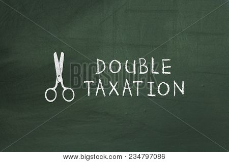 Scissors And Double Taxation Text On Green Chalkboard