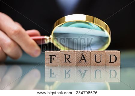 Businessperson Holding Magnifying Glass Over Fraud Blocks