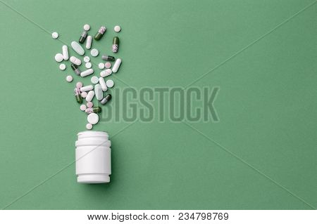 Assorted Pharmaceutical Medicine Pills, Tablets And Capsules And Bottle On Green Background. Copy Sp