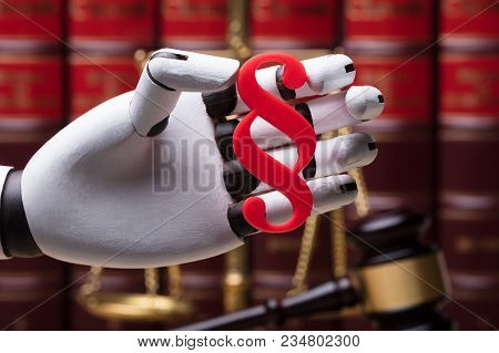 Close-up Of A Robotic Hand Holding Paragraph Symbol In Courtroom