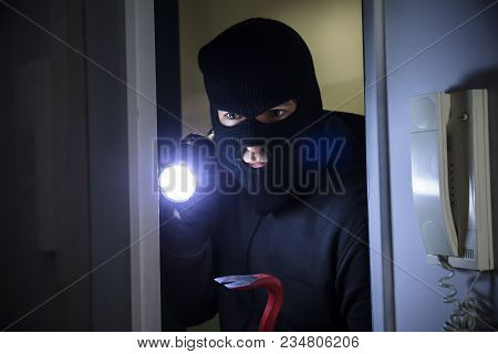 Thief With Flashlight And Crowbar Entering Into House