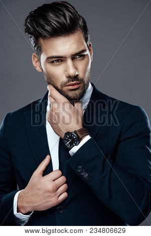 Close-up Handsome And Successful Man In An Expensive Suit. He Is In A White Shirt With A Tie. A Stro