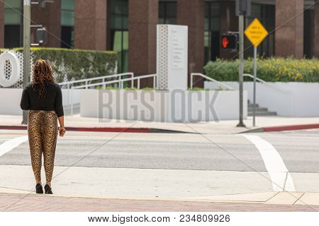 An African-american Woman Standing At Cross Walk Waiting To Cross. No Traffic, No Other People