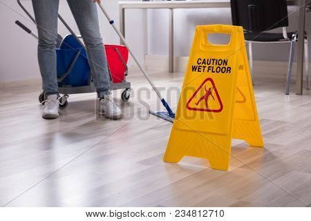 Close-up Of Yellow Wet Floor Caution Sign Near Janitor Cleaning Office