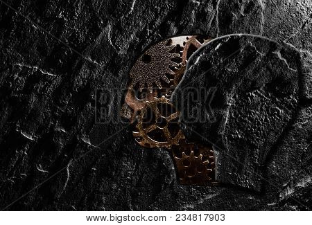 Stone Head Cutout Revealing Gears On Dark Background
