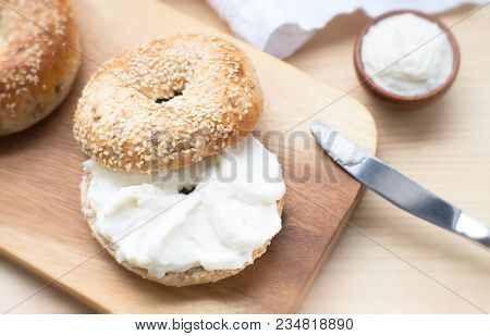 Bagel Sesame With Spread Cream Cheese Close-up On A Wooden Cut Board. Slise Of Delicious Bagel, Gold