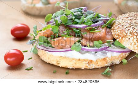 Bagel Sandwich With Creame Cheese, Salmon,onion,tomato,greens,chives Close-up On A Wooden Background