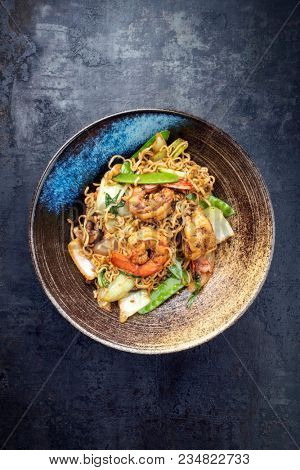 Traditional stir-fried Thai phat mama mie noodles with king prawns and vegetables as top view in a bowl