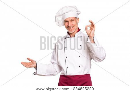 Smiling senior cook showing something isolated on white background. Portrait of happy mature chef presenting over white background. Cheerful chef man looking at camera with hand sign ok.