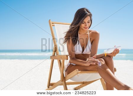 Young woman in white bikini applying suntan lotion while sitting on deckchair. Smiling latin girl applying sunscreen lotion at beach with copy space. Beautiful young woman protect skin from sun.