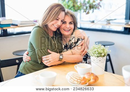 Portrait Of Beautiful And Happy Mother And Daughter In A Restaurant Embracing Each Other