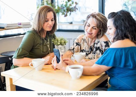 Attractive Hispanic Women Sitting Together At A Coffee Shop And Looking At Smartphone