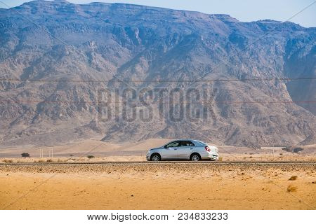 Aqaba, Jordan - December 22, 2017: Car On The Road Against The Background Of Distant Mountain Peaks