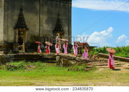Kanchanaburi, Thailand - July 24, 2016: Group Of Mon Nuns In Pink Robes Holding Umbrella Walking Tow