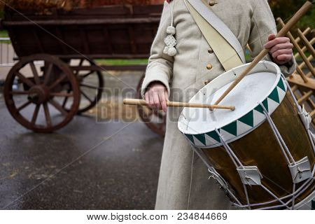 Military drummer dressed in uniform of Napoleonic Wars time beats drumsticks a drum.