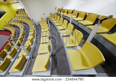 Rows of chairs and microphones in auditorium, side view.