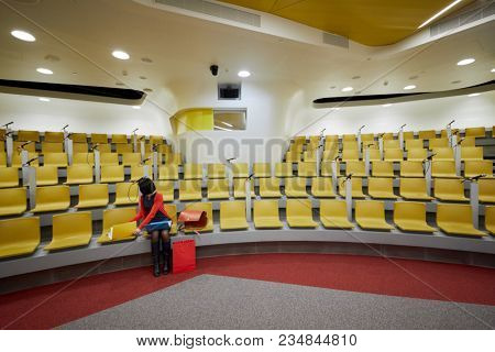Woman sits in auditorium with yellow chairs.