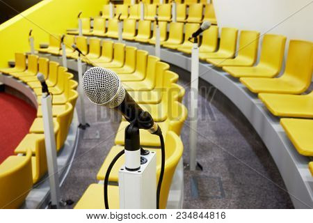 Closeup microphone on holder in conference auditorium.