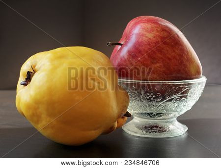 Closeup View Of Ripe Yellow Quince And Juicy Red Apple In Vintage Glass Vase Against A Low Key Backg
