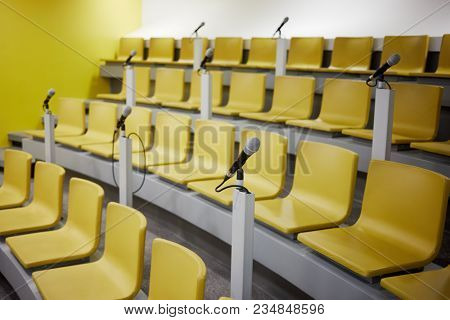 Yellow chairs and microphones in conference auditorium.
