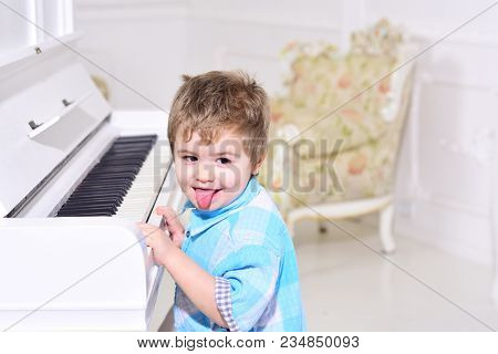 Child Sit Near Piano Keyboard, White Background. Boy Cute And Adorable Puts Finger On Keyboard Of Pi
