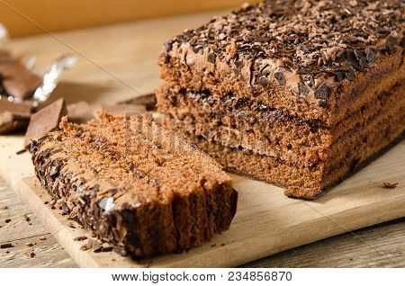 Chocolate Cake. A Piece Of Biscuit Dessert With Chocolate Sprinkling With Chocolate Pieces On A Wood