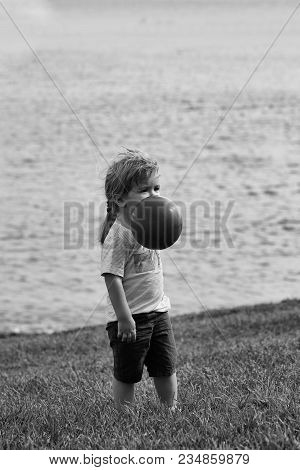 Cute Baby Boy With Blond Hair Ponytail In Blue Tshirt And Shorts Plays With Orange Toy Balloon On Gr