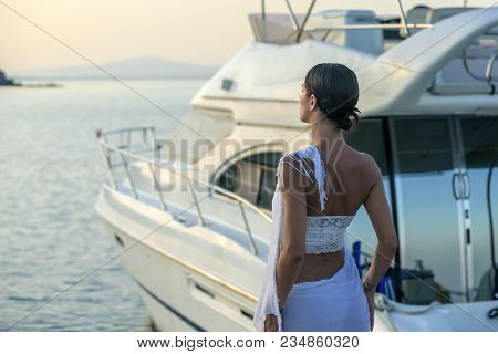 Young Beautiful Brunette Woman Relaxing At Dock Near Boat, Sunset On Summer Day. Woman In Fashionabl