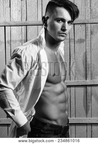 Sexy Serious Sensual Muscular Young Macho Man With Bare Torso In White Shirt Standing Indoor On Wood