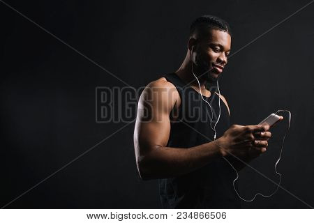 Smiling Muscular African American Man In Earphones Using Smartphone Isolated On Black