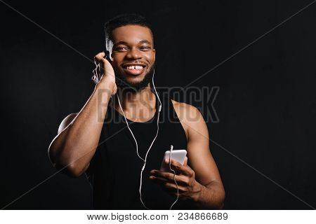 Muscular African American Man In Earphones Using Smartphone And Smiling At Camera Isolated On Black