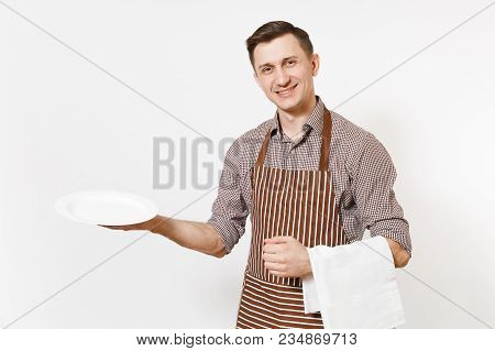 Young Man Chef Or Waiter In Striped Brown Apron, Shirt Holding White Round Empty Clear Plate, Towel