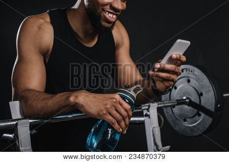 Cropped Shot Of Smiling Young African American Sportsman Holding Bottle Of Water And Using Smartphon