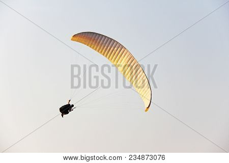 A Paraglider Against The Blue Sky. A Bright Paraglider Flies In The Sky. India, Goa.