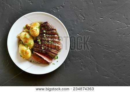 Beef Steak With Potato And Caramelized Onion In Plate On Black Stone Background With Copy Space. Top