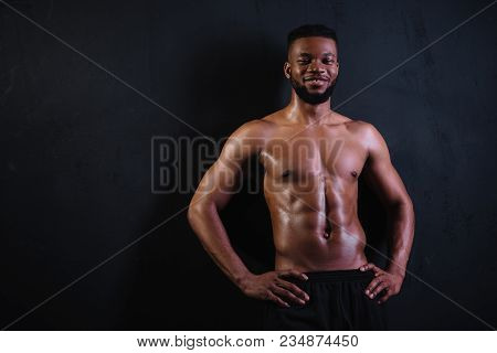 Shirtless Muscular Young African American Man Standing With Hands On Waist And Smiling At Camera On