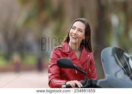 Biker Thinking Looking At Side On Her Motorbike On The Street
