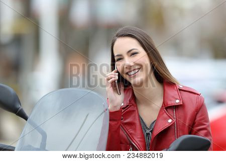 Happy Motorbiker Sittingon Her Motorbike Calling On Phone And Looking At Camera