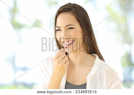 Portrait Of A Happy Woman Taking A Pill Looking Away