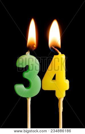 Burning Candles In The Form Of 34 Thirty Four (numbers, Dates) For Cake Isolated On Black Background