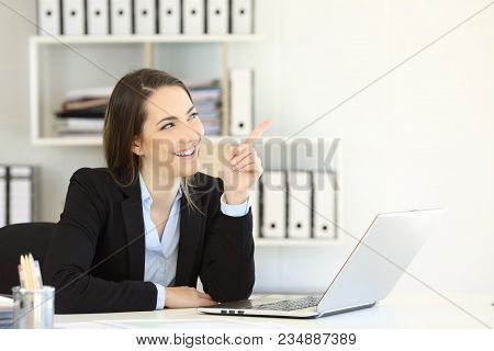 Happy Businesswoman Presenting Something Blank Pointing Above At Office