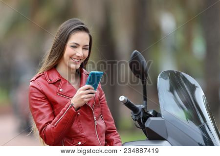 Happy Biker Checking Smart Phone On Her Motorbike On The Street