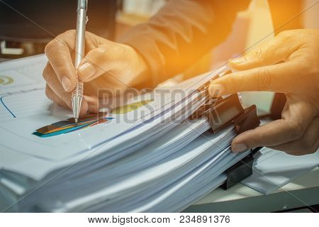 Businessman Preparing Reports Papers With Graphs, Charts On Stacks Of Documents Files For Finance In