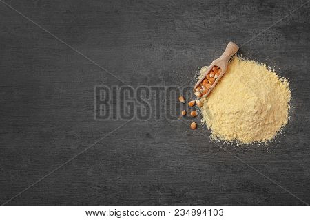 Pile Of Corn Flour And Scoop With Kernels On Gray Background