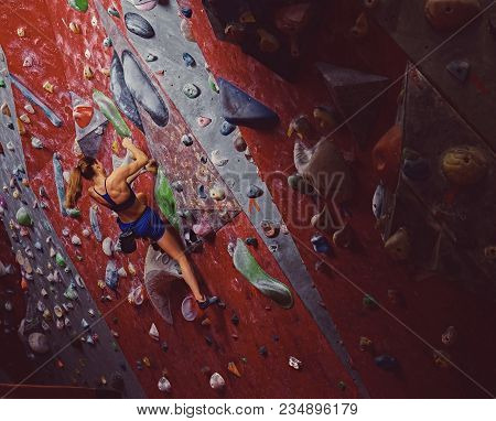 Professional Female Climber On A Bouldering Wall Indoors.