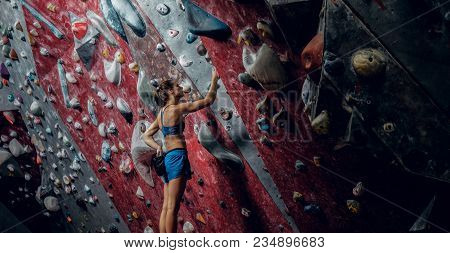Free Climber Female Bouldering Indoors. Back View.