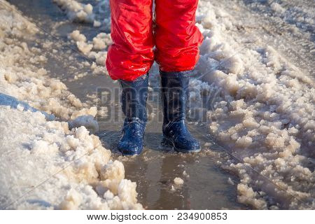 Kid Legs In Blue Rainboots Standing In The Ice Puddle With Melting Snow At Sunny Spring Day, Outdoor